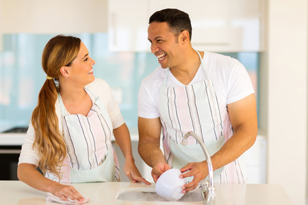 cheerful couple washing dishes together in the kitchen