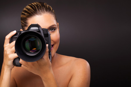 lifestyle caucasian: pretty woman taking picture with digital camera over black background