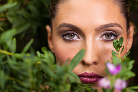 woman from behind: beautiful young woman posing among green leaves Stock Photo