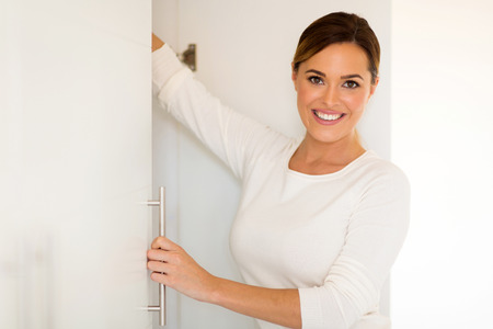 closet door: portrait of pretty woman opening a closet door