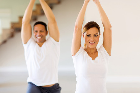 lovely couple: portrait of lovely couple doing yoga exercise at home