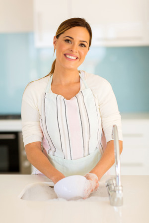 beautiful woman washing dishes in kitchen Stock Photo