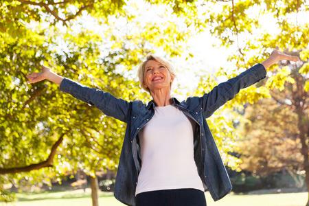 야외에서 뻗은 팔과 행복 중간 나이 여자의 낮은 각도보기 스톡 콘텐츠
