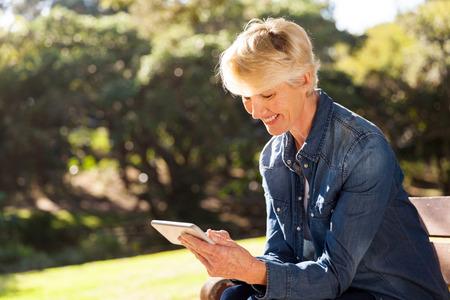 happy senior blond woman texting on smart phone