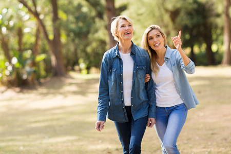 seniors walking: attractive senior mother with daughter relaxing outdoors