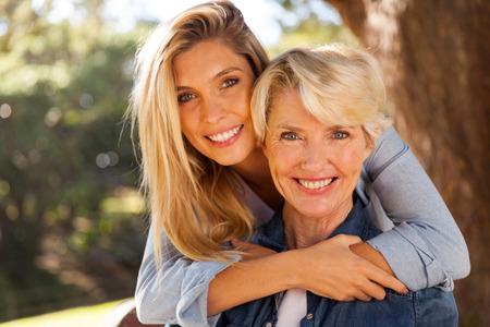 figlia amorevole abbracciando mezza età all'aperto madre