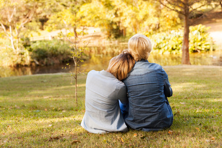 back view of mother and daughter by the pond photo