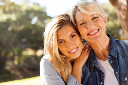 happy middle aged blond mother and adult daughter outdoors Stockfoto