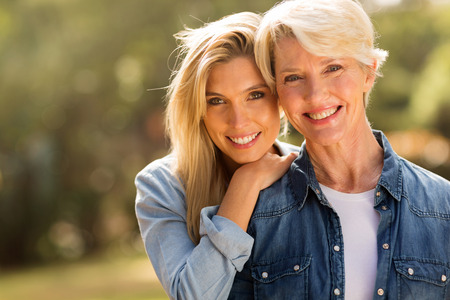 mature mother and young daughter looking at the camera