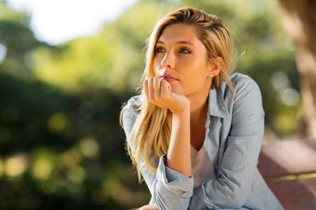 mujer pensando: mujer sentada sola al aire libre Foto de archivo