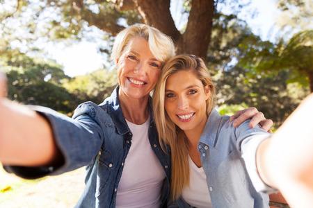 mama e hija: Mujer mayor feliz y su hija teniendo selfie juntos