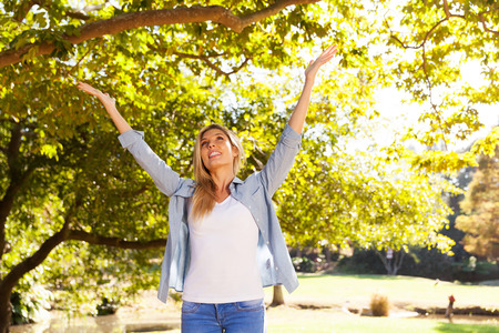lighthearted: happy young woman with arms open under the trees Stock Photo