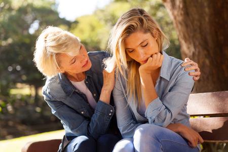 amorevole donna di mezza età che conforta il suo triste figlia al parco