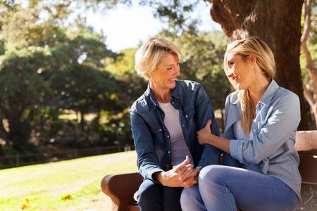 personas hablando: hermosa joven que habla con su mamá mediados de edad al aire libre