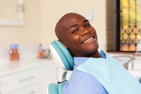 male dentist: african man visiting dentist for dental checkup