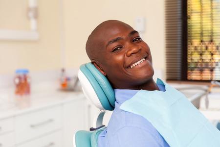 sillon: africano hombre dentista visita para revisión dental
