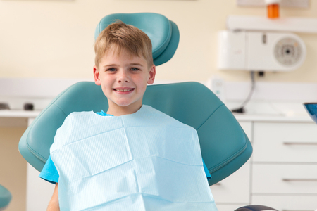 portrait of little boy sitting in dentist's office
