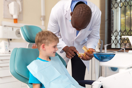 African Dentist Explaining The Dental Procedure To Little Boy Photo
