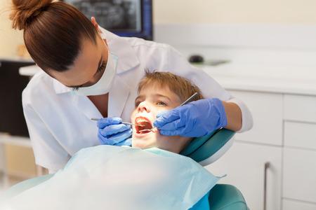 dentista: dentista joven y exitoso examen de los dientes del paciente