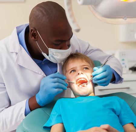 dentista: dentista africano profesional que trabaja en el peque�o paciente