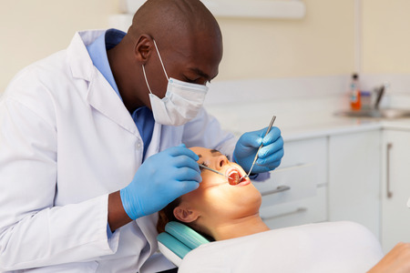 professional male dentist examining woman's teeth Standard-Bild