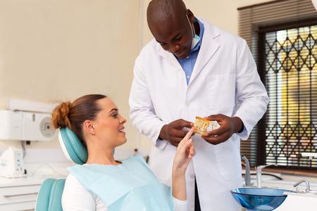odontologo: amigable modelo masculino dentista que muestra los dientes a su paciente