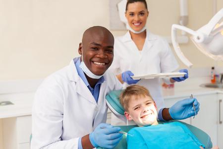 dentista: retrato de equipo médico profesional y paciente joven durante el chequeo dental Foto de archivo