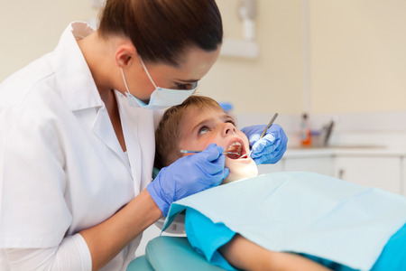 examined: young boy getting his teeth examined in clinic
