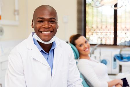 odontologa: dentista hombre africano sonriente con un paciente en el fondo