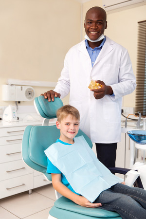 portrait of little boy and african american dentist in office Stock Photo