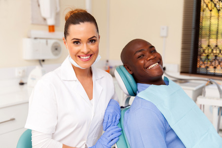 beautiful young female dentist and african patient in office Stock Photo