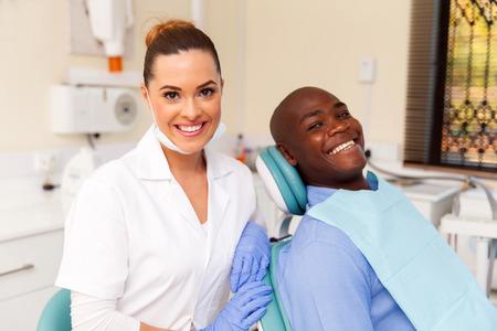 denti: hermosa mujer dentista y el paciente joven africano en la oficina Foto de archivo