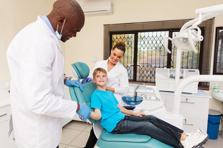 congratulate: friendly dentist congratulate little boy for a successful operation Stock Photo
