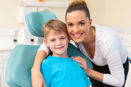 male dentist: beautiful mother hugging her son in dentist office