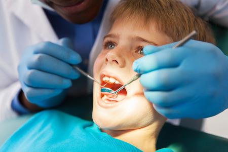 african male dentist examining little boy teeth close up