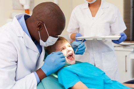 african american male dentist examining patient's teeth in dental clinic