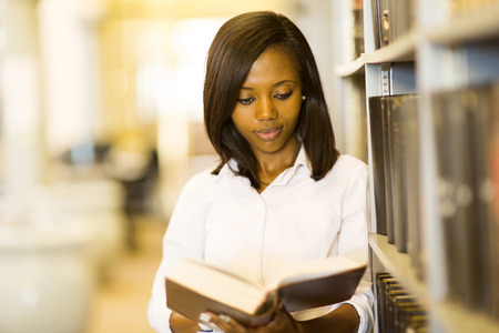 adult student: pretty african college girl reading a book in library Stock Photo