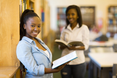 uni: pretty female african uni student holding a book in library