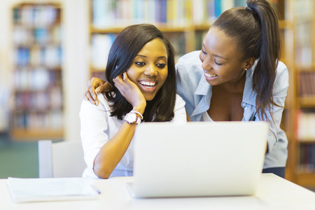 school friends: cheerful african college students using laptop together