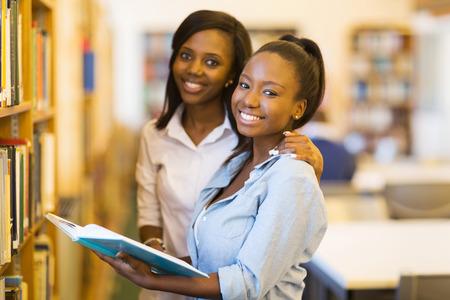 educacion: estudiantes africanos femeninos felices universitarios en la biblioteca Foto de archivo