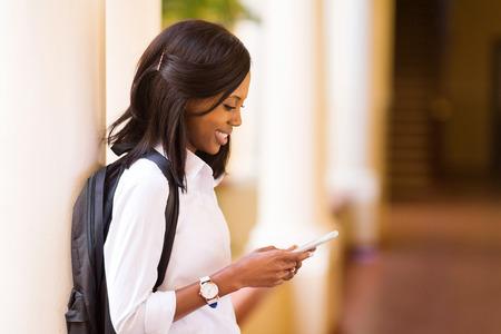 hezká žena afro americký univerzitní student pomocí mobilního telefonu