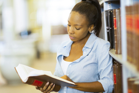 library book: young female african university student reading a book in library