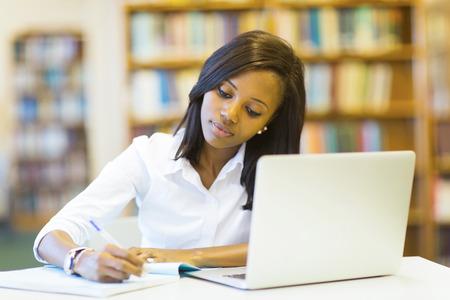 estudiante: bonita estudiante universitaria estudiando en la biblioteca Foto de archivo