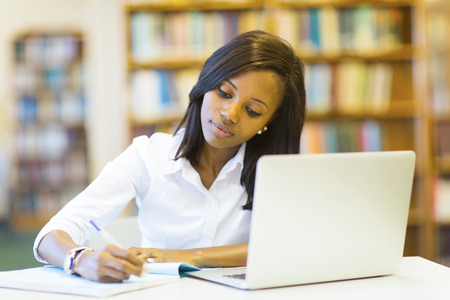 black student: pretty female college student studying in library