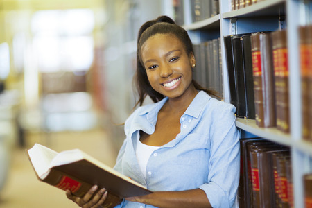 african student: happy female african american college student in library