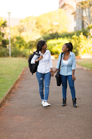 female student: beautiful african american college students walking on modern campus