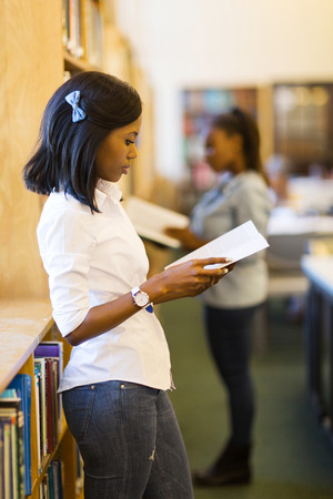 adult student: young african woman reading a book in library