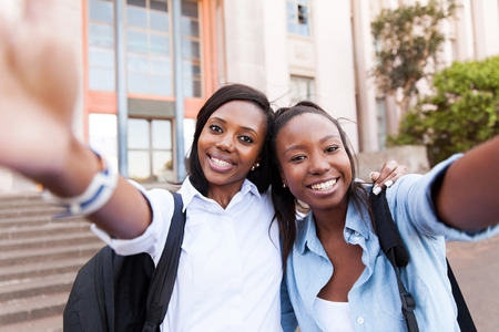 female student: cheerful young college friends taking self portrait on campus