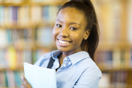 african student: portrait of pretty african college student in library