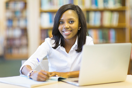 jovenes estudiantes: hermosa estudiante afroamericana sentado en la biblioteca de la universidad Foto de archivo